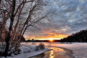 Snow-covered landscape with a small river and the sun low on the horizon.
